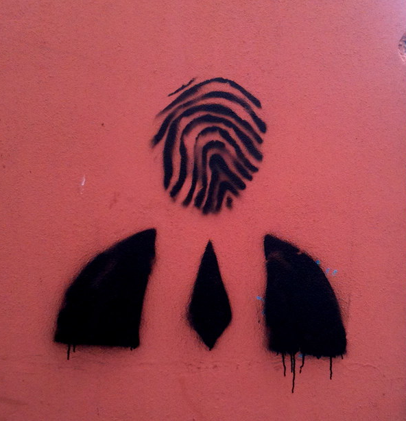 Image is a photo of graffiti on a red wall, the black paint stencil is an outline of a man in a suit with a fingerprint for a head